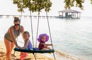 Family playing on the beach at Jubilee Suites in Fairhope, AL
